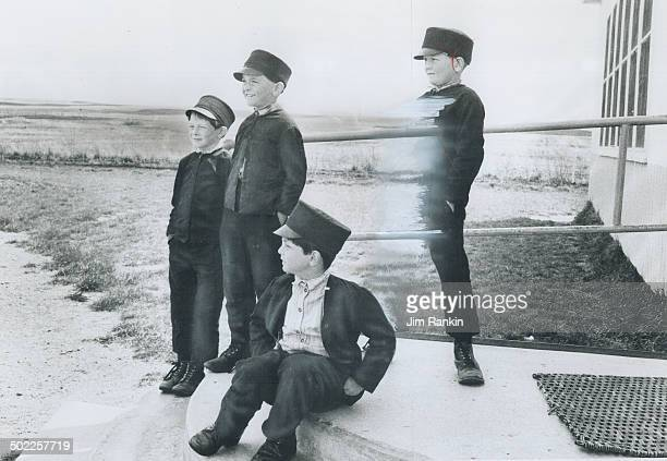 Hutterite Boys wear peaked caps until leaving school at age 14 or 15 Then they're considered men allowed to wear widebrimmed hats and work full time...