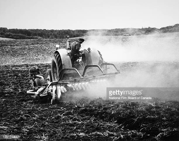 A Hutterite farmer is plowing a large field on the colony of Northeast Alberta Canada 1963 Photo taken during the National Film Board of Canada's...