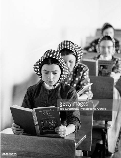 A Hutterite girl concentrates her attention on reading the Wizard of Oz A fundamentalist religious sect Hutterites require females to cover their...