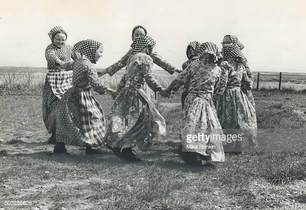 Hutterite girls in everyday dress dance in a circle during school recess in a Saskatchewan settlement