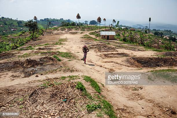 A Hutu girl walks through the rubble of a former Hutu displaced camp in Buleusa on July 16 2016 Tensions are high between Hutus and Kobos since the...