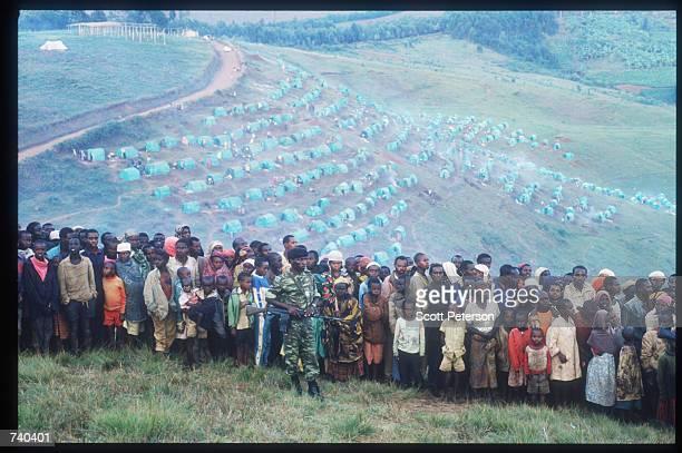 Hutu guard keeps the crowd back June 24, 1994 at the Nyarushishi Tutsi refugee camp on the Zaire border in Gisenyi, Rwanda. The camp is run by Hutu...