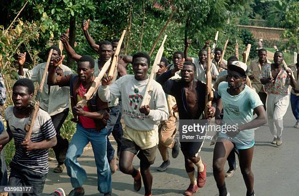 Hutu militiamen practice marching with mock wooden rifles on the road from Goma to Kigali