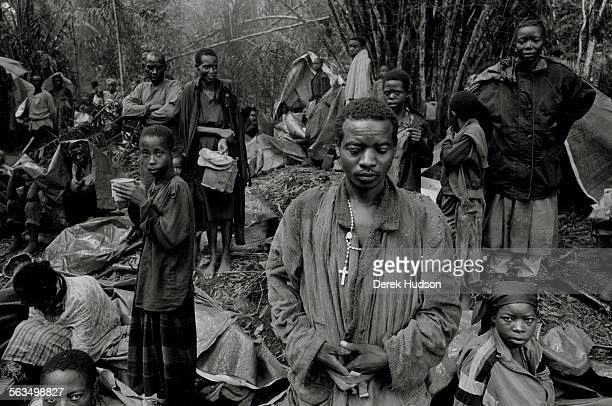 Hutu refugee wearing a Christian cross around his neck stands in a jungle clearing with hundreds of other Hutus on their trek to the Congolese town...