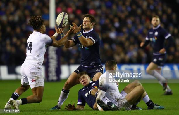 Huw Jones of Scotland takes the ball under pressure from Anthony Watson of England during the NatWest Six Nations match between Scotland and England...