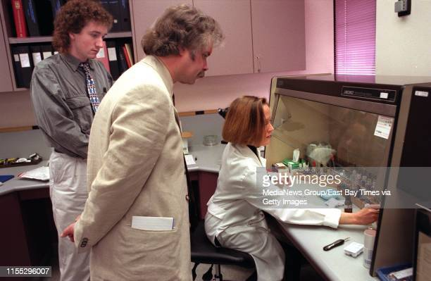 Huw Turk a forensic scientist standing left and Steven Reddick a drugs and product manager standing right look on as Kristie Abbott a Forensic...