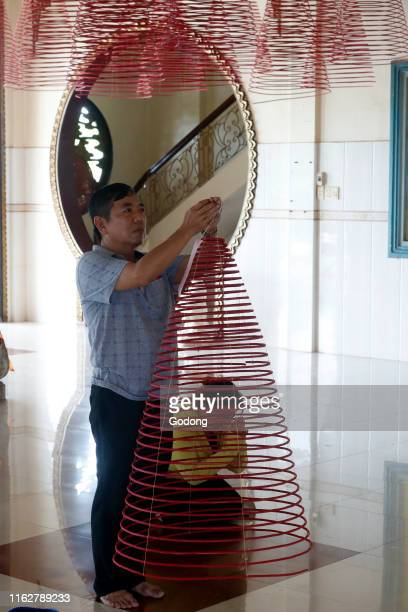 Huynh Dao buddhist pagoda Worshippers with giant Incense coils Chau Doc Vietnam