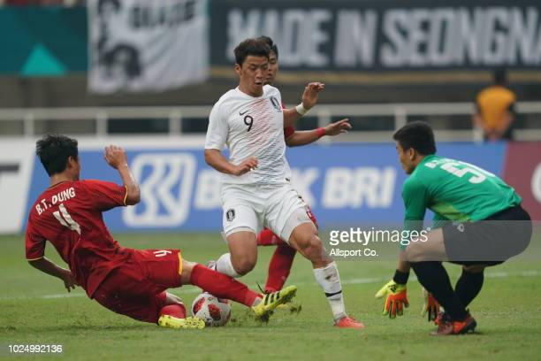 Hwang Hee Chan of South Korea battles Bui Tien Dung of Vietnam during the Men's Footbal semi final competition between Vietnam and South Korea held...