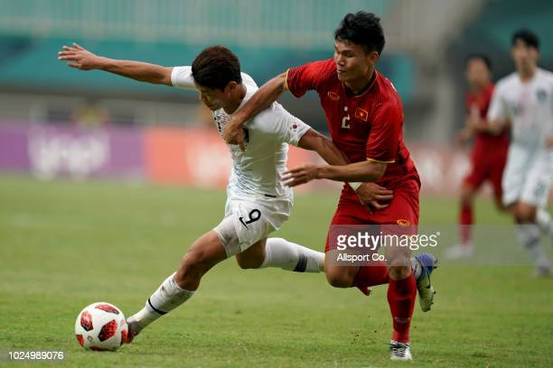 Hwang Hee Chan of South Korea battles Pham Xuan Manh of Vietnam during the Men's Footbal semi final competition between Vietnam and South Korea held...