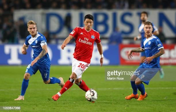 Hwang Heechan of Hamburger SV holds off Nils Butzen of 1FC Magdeburg and Philip Turpitz of 1FC Magdeburg during the Second Bundesliga match between 1...