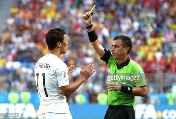 Hwang Heechan of Korea Republic is shown a yellow card by referee with Referee Joel Aguilar during the 2018 FIFA World Cup Russia group F match...