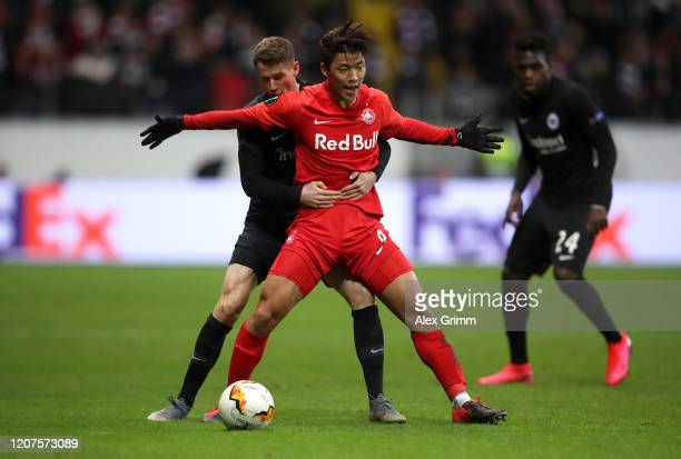 Hwang Heechan of RB Salzburg is tackled by Erik Durm of Eintracht Frankfurt during the UEFA Europa League round of 32 first leg match between...