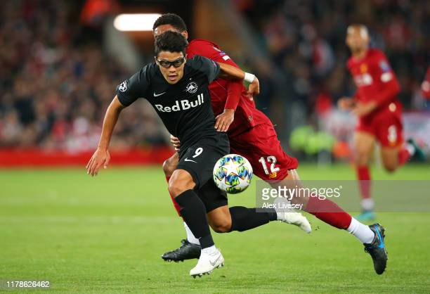 Hwang Heechan of Red Bull Salzburg holds off a challenge from Joe Gomez of Liverpool during the UEFA Champions League group E match between Liverpool...