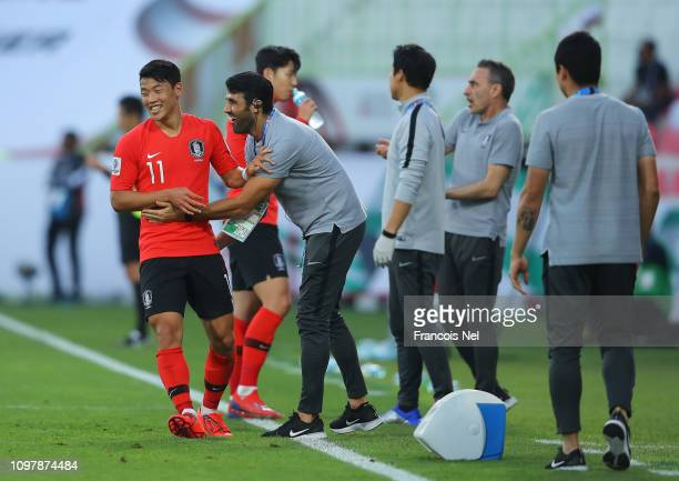 Hwang HeeChan of South Korea celebrates with coaching staff as he scores his team's first goal during the AFC Asian Cup round of 16 match between...