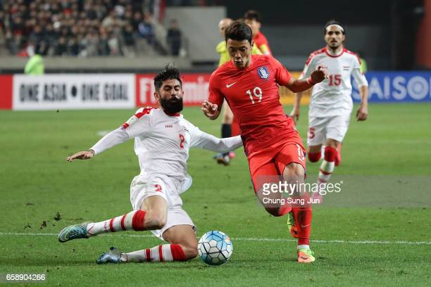 Hwang HeeChan of South Korea competes for the ball with Al Salih Ahmad of Syria during the FIFA World Cup Qualification AFC Final Group Stage match...