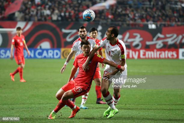 Hwang HeeChan of South Korea competes for the ball with Almasri Hadi of Syria during the FIFA World Cup Qualification AFC Final Group Stage match...