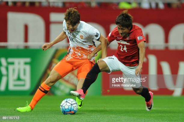 Hwang Ilsu of Jeju United FC and Takahiro Sekine of Urawa Red Diamonds compete for the ball during the AFC Champions League Round of 16 match between...