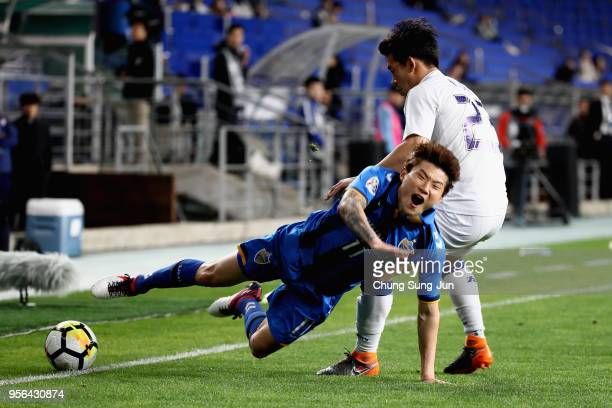 Hwang Il-Su of Ulsan Hyundai is tackled by Lee Ki-je of Suwon Samsung Bluewings during the AFC Champions League Round of 16 first leg match between...