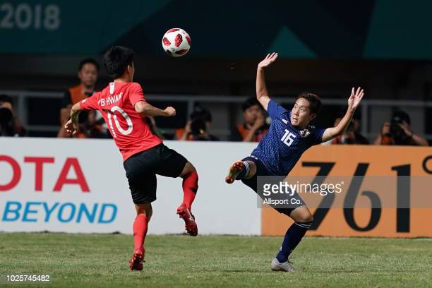 Hwang Inbeom of South Korea battles Watanabe Kouta of Japan during the Men's Football gold medal match between South Korea and Japan at the Pakan...