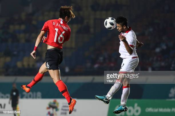 Hwang Ui Jo of South Korean fights for the ball with Sayed Mohamad Shubbar of Bahrain during the Men's Football Group E match between South Korea and...