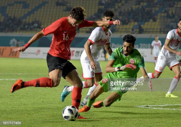 Hwang Uijo of South Korea tussles for the ball against Ammar Ahmed of Bahraini during the football competition of the 2018 Asian Games at the Si...