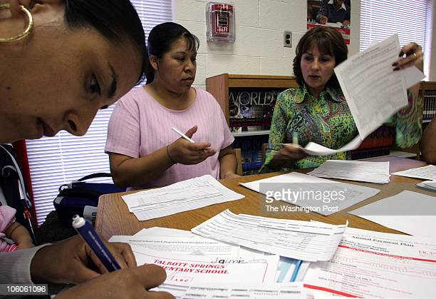 hxforms7 Mark Gail_TWP from the leftGloria Valle Cortes fills out the paperwork as Silvia Jaramillo and Talbott Springs elementary school's ESL...
