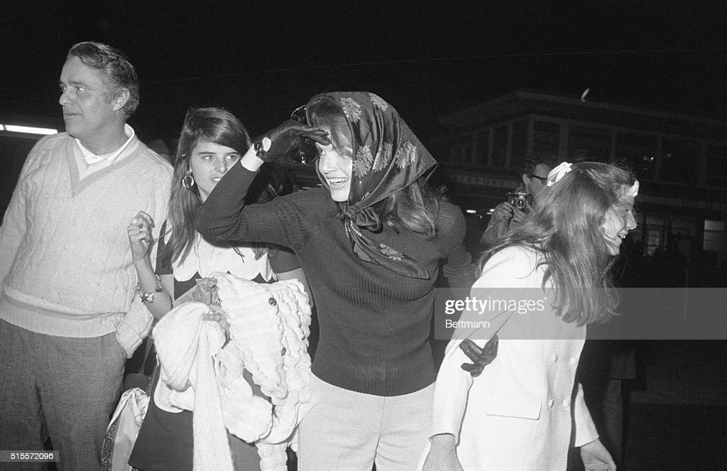 Mrs. Jacqueline Onassis and daughter, Caroline, look both ways as they looked for John Jr., at airport as Kennedy children and other members of the clan arrived late 11/19. They will attend funeral services 11/20 for the late Joseph Kennedy who died 11/18.