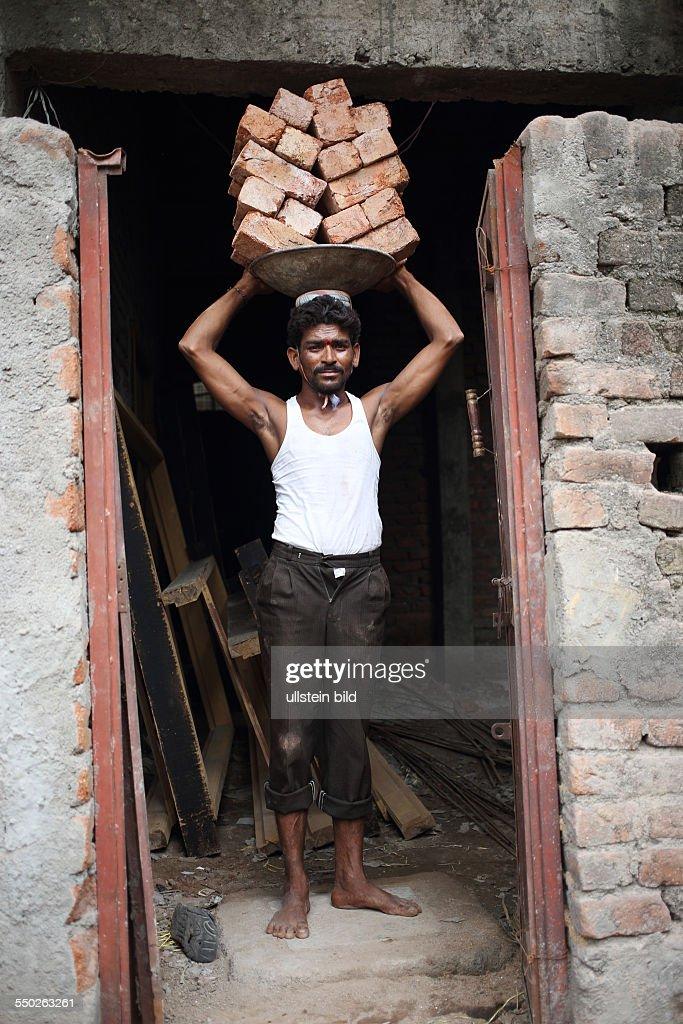 IND, Hyderabad, 20130726, Arbeiter mit Ziegelsteinen : News Photo