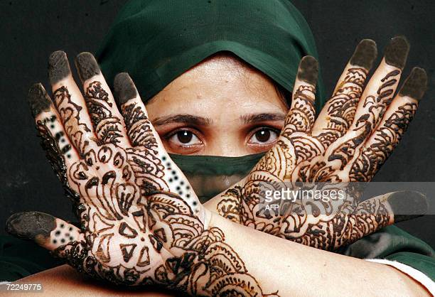 An Indian Muslim woman poses showing her hands decorated with Mehendi during 'Chand Raat' or 'Night of the Moon' in Hyderabad 24 October 2006...