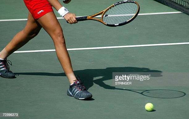 The shadow of Indian tennis player Sania Mirza falls onto the court during a practice session at The Lal Bahadhur Tennis Stadium in Hyderabad 18...