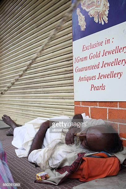 IND Hyderabad Sadhu schläft vor einem geschlossenen Schmuckgeschäft