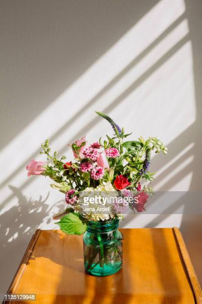 hydrangea and wildflower bouquet in mason jar vase on vintage table - jena rose stockfoto's en -beelden