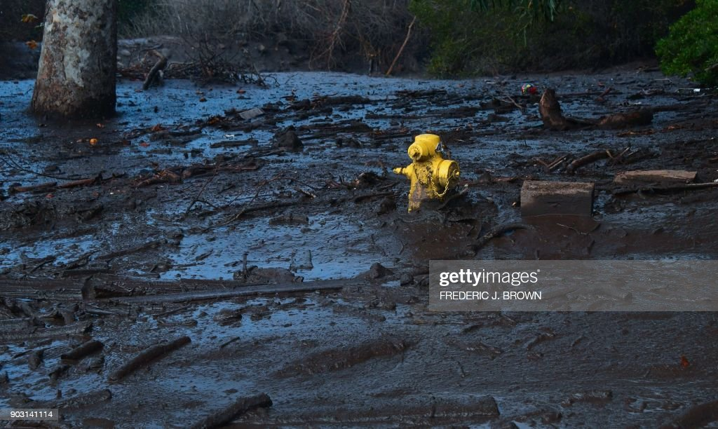 TOPSHOT - A hydrant is almost covered in mud which came down hillsides from overnight rain in Montecito, California on January 9, 2018. Mudslides unleashed by a ferocious storm demolished homes in southern California and killed at least 13 people, police said Tuesday. /