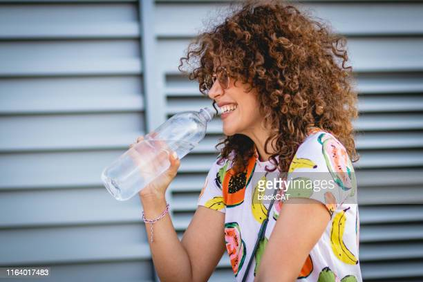 hydration during the summer. a young woman drinks water - bibita foto e immagini stock