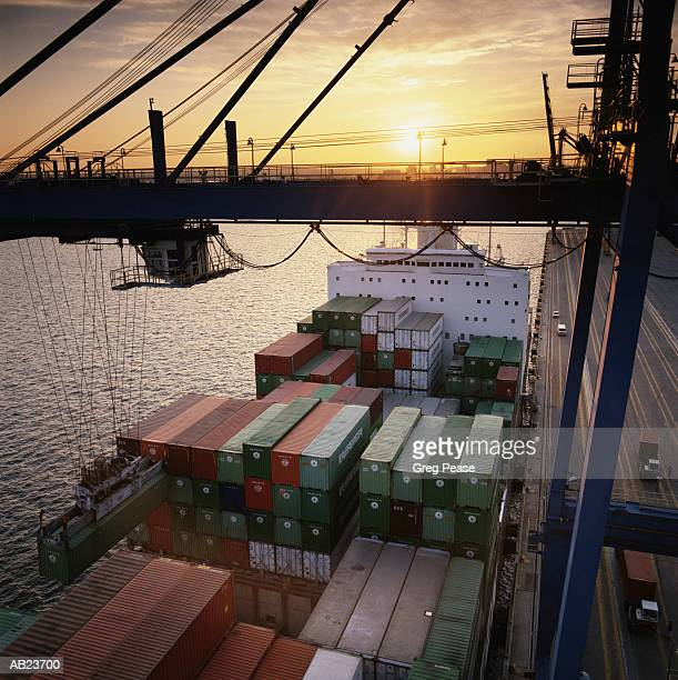 """hydraulic cargo crane loading freighter, sunset, elevated view - """"greg pease"""" stock pictures, royalty-free photos & images"""