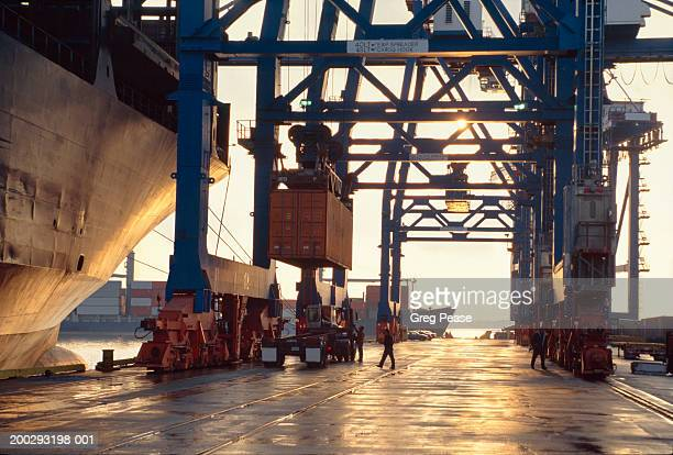 """hydraulic crane unloading shipping containers, evening - """"greg pease"""" stock pictures, royalty-free photos & images"""