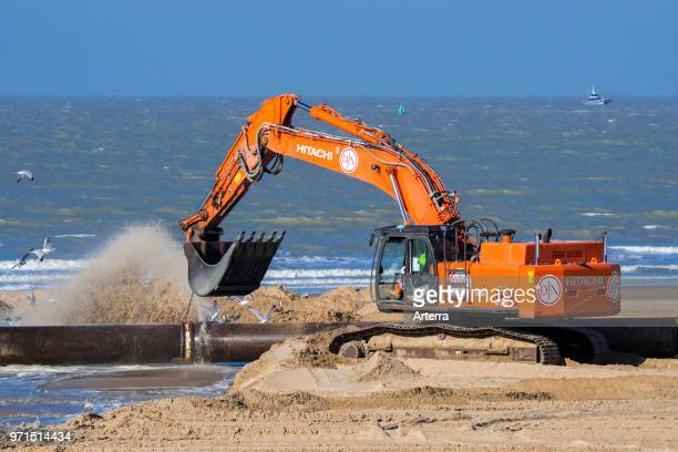 Hydraulic excavator connecting pipes of pipeline during sand replenishment / beach nourishment works along the Belgian coast at Ostend Belgium