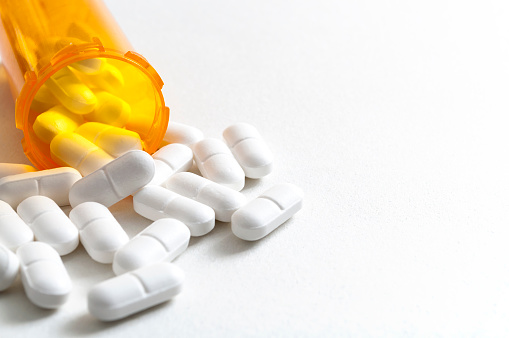 Hydrocodone capsules spilling out of a prescription bottle with copyspace 938938858