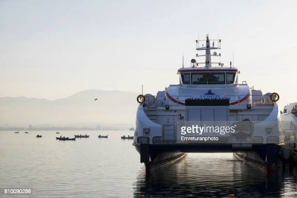 hydrofoil passenger boat and fishing boats behind in the bay of izmir early in the morning. - emreturanphoto stock pictures, royalty-free photos & images