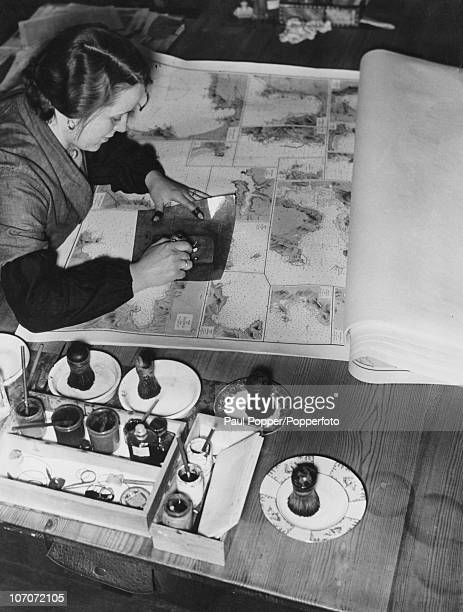 A hydrographer prepares maps for German submarine crews during World War II circa 1940 She is checking and filling in the register numbers of...