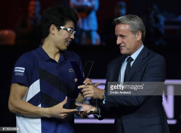 Hyeon Chung of South Korea is rewarded by ATP World Tour Executive Chairman and President Chris Kermode at the end of the mens final on day 5 of the...