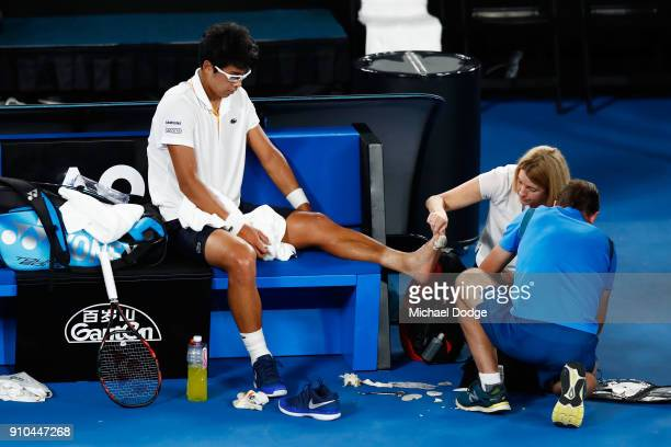 Hyeon Chung of South Korea receives medical attention for an injured foot in his semifinal match against Roger Federer of Switzerland on day 12 of...