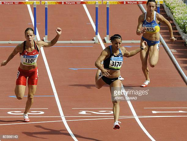 Hyleas Fountain of the US crosses the finish line next to Canada's Jessica Zelinka and Ukraine's Ganna Melnichenko of the women's Heptathlon 100m...