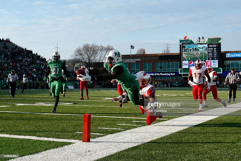 Hyleck Foster #2 of the Marshall Thundering Herd dives into the end zone with a 25-yard touchdown in overtime against the Western Kentucky Hilltoppers at Joan C. Edwards Stadium on November 28, 2014 in Huntington, West Virginia. Western Kentucky defeated Marshall 67-66 on a two-point conversion in overtime to hand them their first loss of the season.