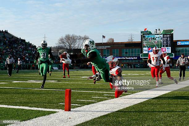 Hyleck Foster of the Marshall Thundering Herd dives into the end zone with a 25yard touchdown in overtime against the Western Kentucky Hilltoppers at...