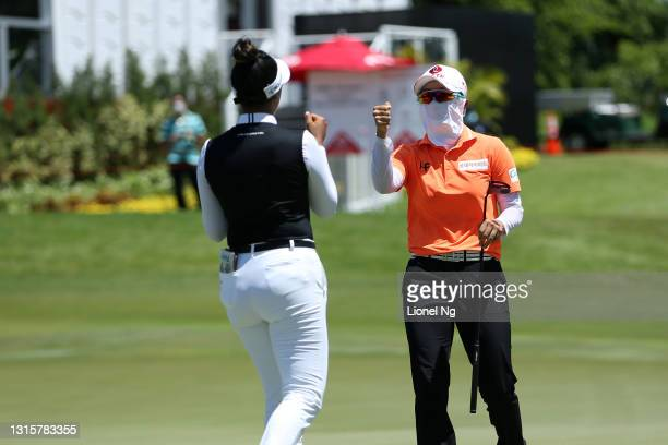 Hyo Joo Kim of South Korea fist bumps with Patty Tavatanakit of Thailand after holing out on the 18th green during the final round of the HSBC...