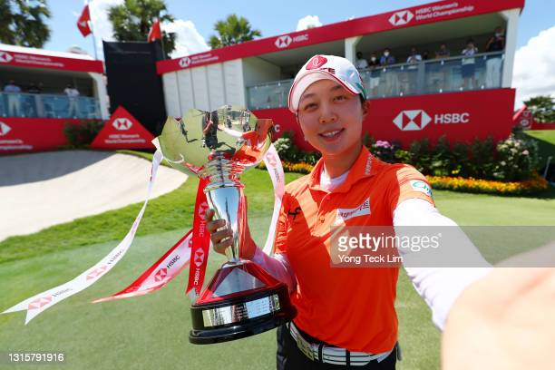 Hyo Joo Kim of South Korea imitates a selfie with the winner's trophy after winning the HSBC Women's World Championship at Sentosa Golf Club on May...