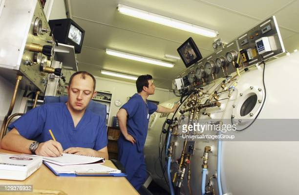 Hyperbaric technologist speaking to patient in chamber through radio human handset The technologist is able to see the patient through a monitor as...