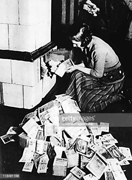 Hyperinflation in Germany post World War I Woman uses bank notes to fuel a stove