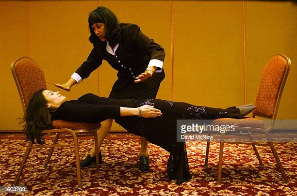 Hypnotherapist and actress Cathy Kay is stretched between chairs after becoming rigid as a board under the hypnotic suggestion of Shelley Stockwell...